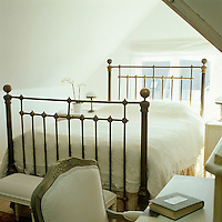 This small, light attic bedroom is fully furnished with a large wrought-iron bed and a desk