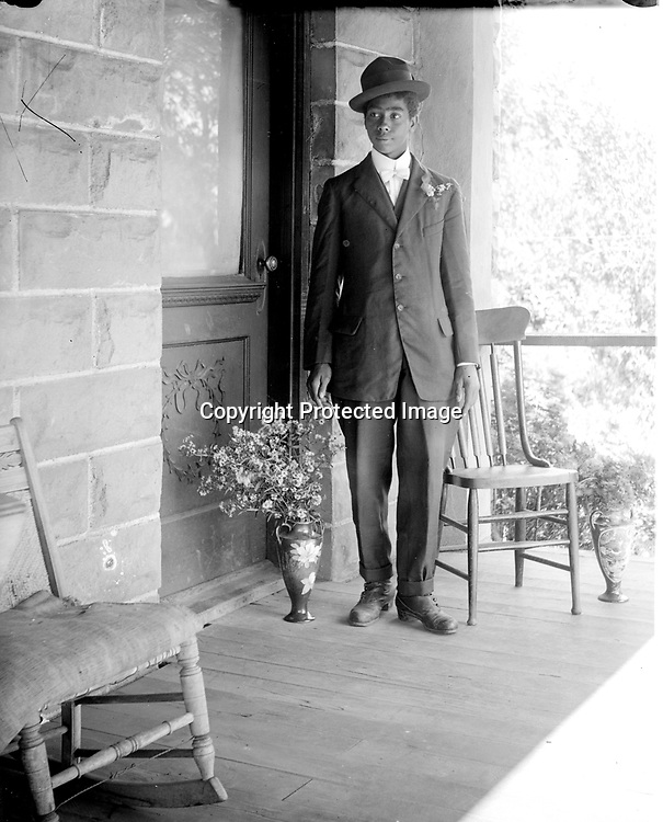 YOUNG MAN WITH FLOWERS.<br /> This young man has flowers pinned to his lapel, as well as in a vase at his feet. The same porch and vase are seen in the two preceding images, but this gentleman's identity is unknown. He is not Dorothy Loving's husband Clayton Lewis.<br /> <br /> Photographs taken on black and white glass negatives by African American photographer(s) John Johnson and Earl McWilliams from 1910 to 1925 in Lincoln, Nebraska. Douglas Keister has 280 5x7 glass negatives taken by these photographers. Larger scans available on request.