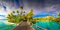 Wooden bridge to paradisiac palm tree motu and beach in luxury Bora Bora lagoon honeymoon destination, near Tahiti, French Polynesia, Pacific Ocean
