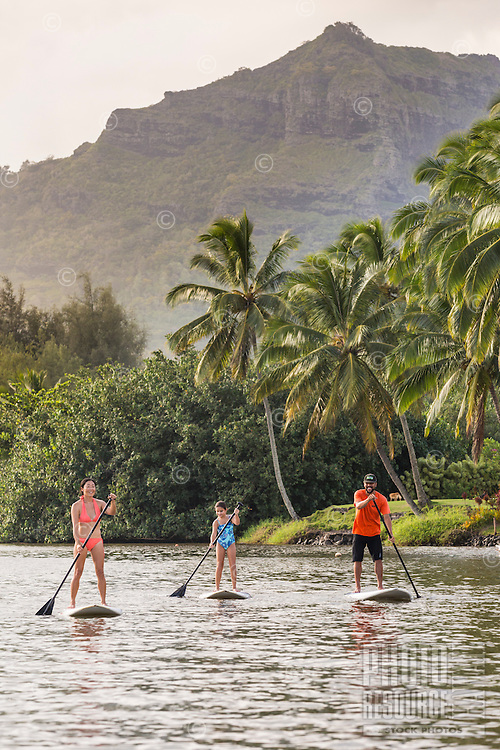 A family learns to standup paddle at Wailua River, Kaua'i.