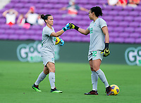 ORLANDO, FL - FEBRUARY 18: Aline #12 of Brazil fist bumps Leticia #22 during a game between Argentina and Brazil at Exploria Stadium on February 18, 2021 in Orlando, Florida.