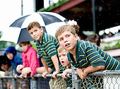 Kids watch the races between rain drops on opening day.
