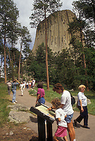 AJ3551, Devils Tower, Devils Tower National Monument, Wyoming, People walk up the Tower Trail to view the spectacular Devils Tower National Monument in the state of Wyoming. Mother and daughter reading informative sign about Devils Tower.