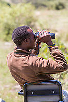 Tanzania. Serengeti Game Spotter Searching for Game with Binoculars.