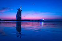 Colorful twilight over the iconic Burj Al Arab hotel, reflecting on Jumeirah beach and Persian Gulf Sea at low tide, in Dubai, United Arab Emirates