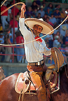 A Mexican cowboy on horseback swings his lasso at the Charros Rodeo Fiesta Event. San Antonio, Texas.
