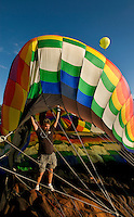 A man steadies a balloon as it's being filled with hot air. Thousands of hot air balloon enthusiasts turn out each year for the annual Carolina BalloonFest, held each fall in Statesville, NC.