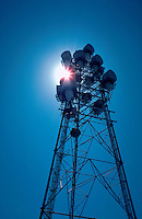 Microwave telecommunications tower, backlit by sun