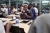 Judith Mbithuka, a casual worker, assembles bank brochures printed at Colourprint in Nairobi, Kenya.