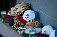 A Burlington Sock Puppets hat sits on top of a glove on the bench in the home dugout during the game against the Bluefield Ridge Runners at Burlington Athletic Park on June 8, 2021 in Burlington, North Carolina. (Brian Westerholt/Four Seam Images)