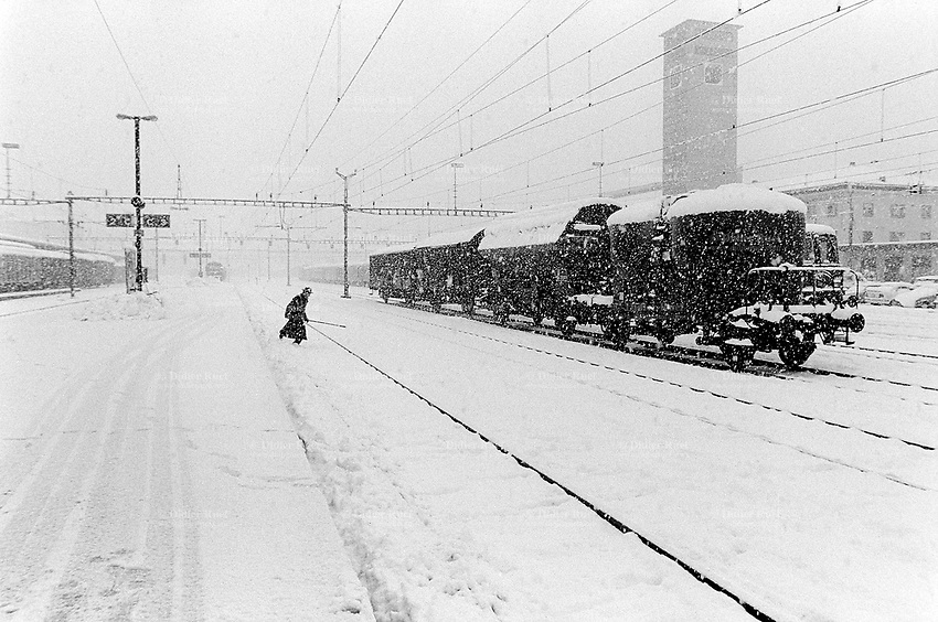 Switzerland. Canton Valais. Sion. Snow storm on the railway station in the winter. A goods train (freight train) is stopped on the rails. A railwayman is crossing the tracks. Snowy season.  © 1995 Didier Ruef