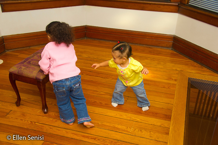 MR / Schenectady, NY. Infant in early walking stage (girl, 11 months, African American & Caucasian) exhibits 11-month-old human development milestone behavior as she balances herself and tries to reach footstool, while her sister (2, African American & Caucasian) is moving it away from her. MR: Dal5, Dal4. ID: AL-HD. © Ellen B. Senisi