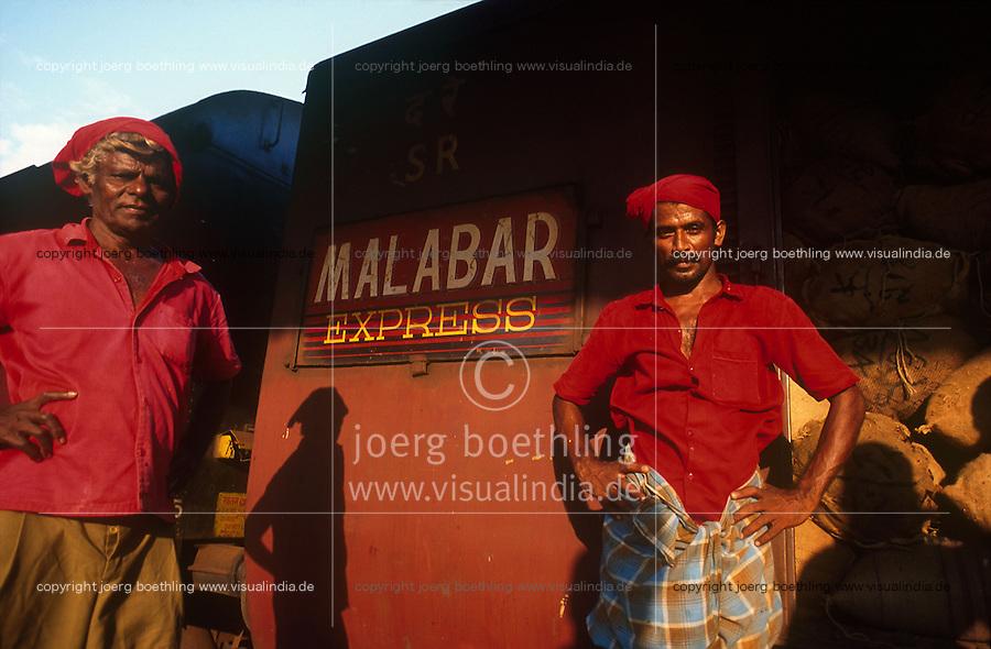 INDIA Karnataka, Mangaluru, Mangalore, porter at railway station, Malabar express a train which runs between Mangalore and Trivandrum along the Malabar coast / INDIEN Mangalore, Gepäckträger in roter Kleidung am Bahnhof, Zug Malabar Express