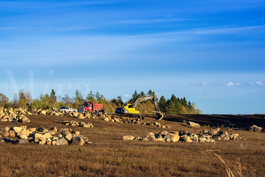 Crane harvests granite boulders from the landscape, Harrington, Maine, USA