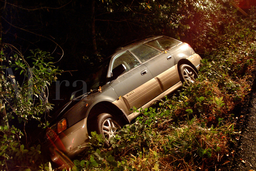 Vehicle accident at night with a car laying on its side in a ditch