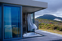 The plate-glass windows of this dramatic bathroom slide back to expose the sunken bath to the elements