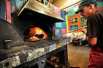 Mark Shriver pulls a pizza out of the wood fired oven at Amicas Pizza. The restaurant also has a micro brewery. Michael Brands for The New York Times.