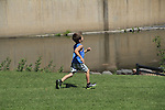 Boy running in an urban park, Denver, Colorado. .  John offers private photo tours in Denver, Boulder and throughout Colorado. Year-round Colorado photo tours.