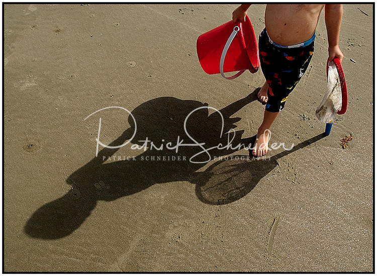 Only his shadow is visible as a boy walks along a sandy beach. Photo taken on Sullivan's Island near Charleston, SC.  Model released image may be used to illustrate other destinations or concepts.