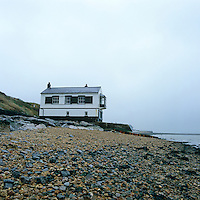 A black and white coastguard's cottage with a bay window overlooking the sea is located on a shingle beach on the English coast