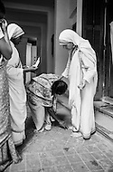 """January 1976, Calcutta, India --- Mother Teresa visits patients at her free hospice for the poor in Calcutta. The first Home for the Dying opened in 1952 and was a free hospice for the poor. Mother Teresa (Agnes Gonxha Boyaxihu) the Roman Catholic, Albanian nun revered as India's """"Saint of the Slums"""", was awarded the 1979 Nobel Peace Prize. --- Image by © JP Laffont"""