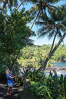 A tourist with a selfie stick takes photos along the coastline at Hawaii Tropical Botanical Garden, Hamakua coastline, Big Island of Hawaiʻi.