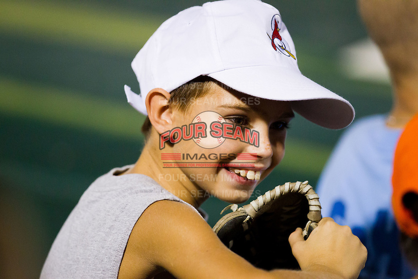 A young fan smiles while talking with friends during a game between the Arkansas Travelers and the Springfield Cardinals at Hammons Field on July 25, 2012 in Springfield, Missouri. (David Welker/Four Seam Images)