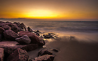 Fine Art Landscape Photograph. Scenic Photograph of a misty morning sunrise with the ocean waves swirling around the rocks on the beaches of Puerto Vallarta, Mexico.