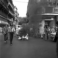 Carrefour de l'avenue d'Alsace-Lorraine et de la rue Lafayette. 5 septembre 1975. Au 1er plan feu et fumée au milieu de la route (pneus), plusieurs hommes à côté ; au 2nd plan foule sur les trottoirs de chaque côté de la rue Lafayette regarde la scène ; en arrière-plan perspective de la rue Lafayette, haut des arbres de la place Wilson. Cliché pris lors d'une manifestation contre le Général Franco.