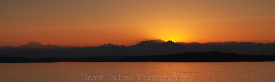 The sun sets over the Olympic mountain range as seen across Puget sound