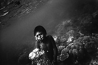 MOKEN BOY..A Moken boy rises to the surface in the coral beds around Surin Islands. The Moken are a nomadic tribe who live on these islands 60 km off the coast of Thailand. Recent scientific studies have shown that the underwater eyesight of Moken children is more than50% percent better than the underwater eyesight of other children. Scientists believe that the Moken train their eyes to see better out of necessity, they have to hunt for fish, and also make out things on the sea bed far below them. Experiments are now underway in Sweden to see if other children can train their eyes in a similar way.