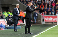SWANSEA, WALES - MAY 17: Swansea manager Garry Monk (R) shouts instructions to his players, Manchester City manager Manuel Pellegrini stand impassive in the background during the Premier League match between Swansea City and Manchester City at The Liberty Stadium on May 17, 2015 in Swansea, Wales. (photo by Athena Pictures/Getty Images)