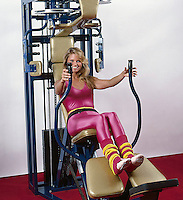 Christie Brinkley on exercise machine wearing hot pink leotard and striped leg warmers. Los Angeles, 1982. Photo by John G. Zimmerman