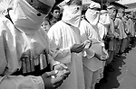 """Masked Hamas militants, dressed as """"martyrs"""" for an honor guard while wearing mock ups of a suicide-bomber's """"belt of explosives"""" pray during the funeral of their slain leader Abdel Rahman Hamad October 14, 2001 in the West Bank town of Qalqilya, hours after the Islamic activist was gunned down by Israeli special forces. Israeli military sources said that Hamad was responsible for two suicide bombings earlier this year which killed 25 young people, mostly at the Dolphinarium Discotheque in June. The targeted killing of one of Israel's """"most wanted"""" has dealt a blow to America's attempts to get Israel and the Palestinians to end their year-long violent conflict which threatens Middle East support for the """"War on terror"""" launched after the September 11 attacks on the United States. Photo by Quique Kierszenbaum"""