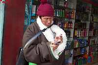A Tibetan man checks his cellphone in the town of Rebgong (Chinese name - Tongren) on the Qinghai-Tibetan Plateau. China.