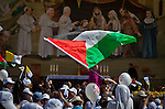 A nun waves the Palestinian flag before Pope Francis celebrates mass with thousands of worshipers in Manger Square in the West Bank city of Bethlehem Sunday May 25 2014. Pope Francis is on a three day visit to the region. Photo by Eyal Warshavsky