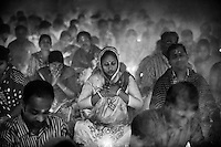 "During Kartik, ""the holiest month"" beginning every year with the new moon in November, thousands of Hindu devotees celebrate the feast of Rakher Upobash, fasting and praying the gods sitting before the Shri Shri Lokanath Brahmachari Ashram, among the Swami Bagh Temple near Dhaka, Bangladesh. The worshippers offer candles called Prodip, meditate, give to charity, and generally perform austerity. <br /> The faithful pray while thick clouds of incense raise into the air.<br />  Barodi, Dhaka, Bangladesh. Nov. 11, 2014"