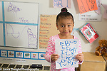 Preschool 3-4 year olds proud girl holding up sheet of letters she wrote