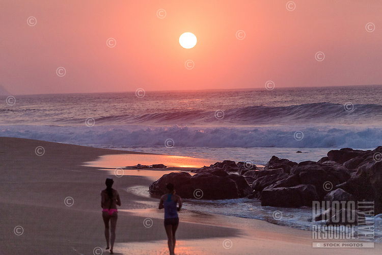 An orange sunset with women jogging near rocks on the shore at Rock Piles beach on the North Shore, O'ahu