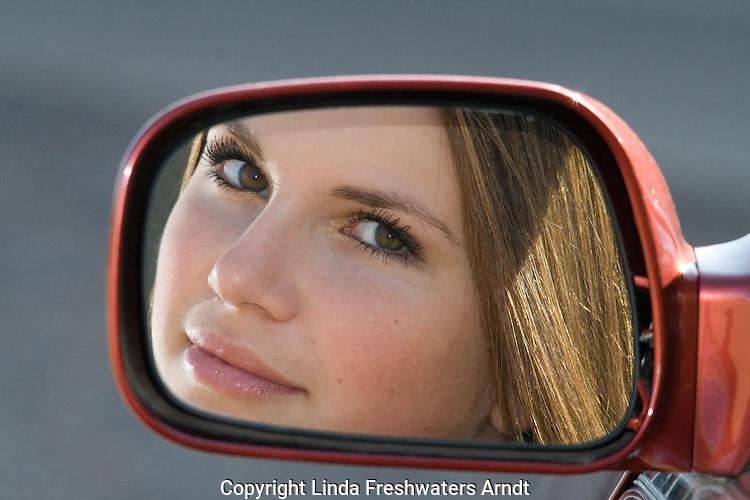Teenager looking in car mirror
