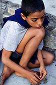 Rio de Janeiro, Brazil. Homeless street child crouching in the gutter.