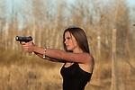 Young woman shooting a handgun