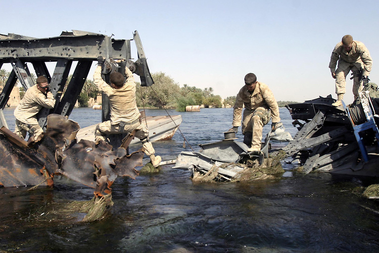 BARWANA, Iraq- Lance Cpl. William J. Quimby Jr., a Marine from 1st Combat Engineers Battalion carries a reel of demolition cord across a damaged section of a bridge that connects the city of Barwana to Haditha. The bridge was originally damaged by an air strike, preventing automobiles to cross, but the engineers are tasked with using demolition to destroy enough of the bridge to prevent any crossing by foot. The Marines of Regimental Combat Team 2 conduct counter-insurgency operations with Iraqi Security Forces to isolate and neutralize anti-Iraqi forces, to support the continued development of Iraqi Security Forces, and to support Iraqi reconstruction and democratic elections in order to create a secure environment that enables Iraqi self-reliance and self-governance. (Official USMC photo by Lance Cpl. Shane S. Keller)