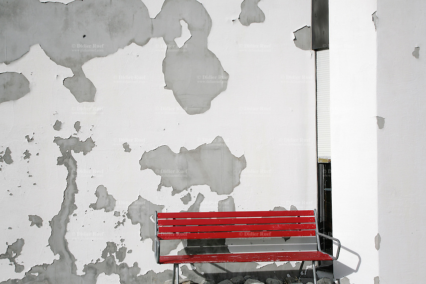 Switzerland. Canton of Ticino. Val di Blenio (Blenio valley). Lucomagno (Lukmanier) pass. A red bench near a white wall. The wall's painting is falling down.  © 2006 Didier Ruef