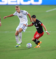 WASHINGTON, DC - AUGUST 25: Joseph Mora #28 of D.C. United battles for the ball with Adam Buska #9 of New England Revolution during a game between New England Revolution and D.C. United at Audi Field on August 25, 2020 in Washington, DC.