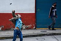 CALARCA - COLOMBIA, 30-04-2021: Un manifestante lanza una piedra en los enfrentamientos con la policía antidisturbios en Calarcá en la vía que conduce al alto de La Línea durante el tercer día de Paro Nacional en Colombia hoy, 30 abril de 2021, y que comenzó el pasado 28 de abril de 2021 para protestar por la reforma tributaria que adelanta el gobierno de Ivan Duque además de la precaria situación social y económica que vive Colombia. El paro fue convocado por sindicatos, organizaciones sociales, estudiantes y la oposición. / A protestor trows a stone in clashes with riot police at the exit of Calarcá on the road that leads to the top of La Línea during the third day of the National Strike in Colombia today, April 30, 2021, and which began on April 28, 2021 to protest the tax reform that the government of Ivan Duque is also advancing of the precarious social and economic situation that Colombia is experiencing. The strike was called by unions, social organizations, students and the opposition in Colombia. Photo: VizzorImage / Santiago Castro / Cont