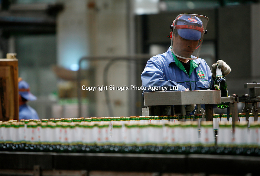 A worker checks for defects on a bottling line of the Tsingtao Brewery in Qingdao, Shandong Province, China. Established in 1903 by German entrepreneurs, Tsingtao Brewery is now China's largest beer manufacturer..
