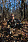 Hunter poses with his custom-made recurve bow and arrow and his harvested buck in northern Wisconsin.