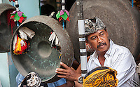 Bali, Indonesia.  Balinese Hindu Playing a Gong in a Village Gamelan Orchestra.