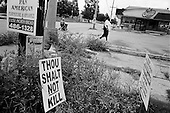 """New Orleans, Louisiana.USA.August 1, 2006..With crime on the rise in much of New Orleans """"Thou Shalt Not Kill"""" signs were placed in a busy intersection nearly one year after hurricane Katrina hit and the levees broke leaving 80% of the city flooded.."""